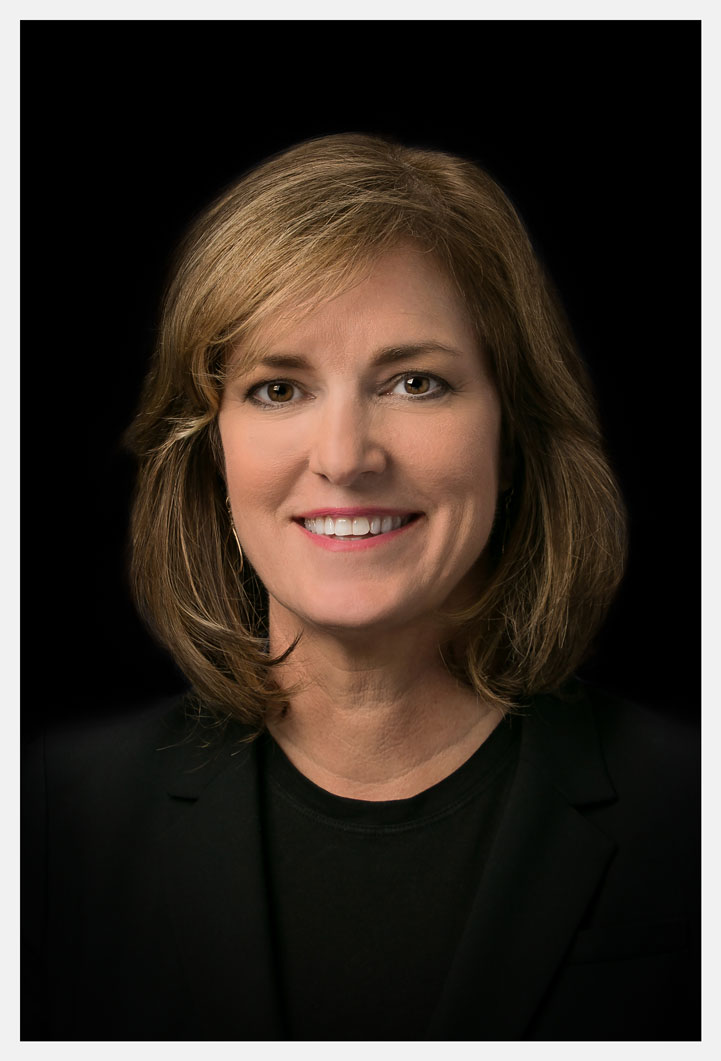 Professional Headshot of Executive Woman Smiling on Black Background
