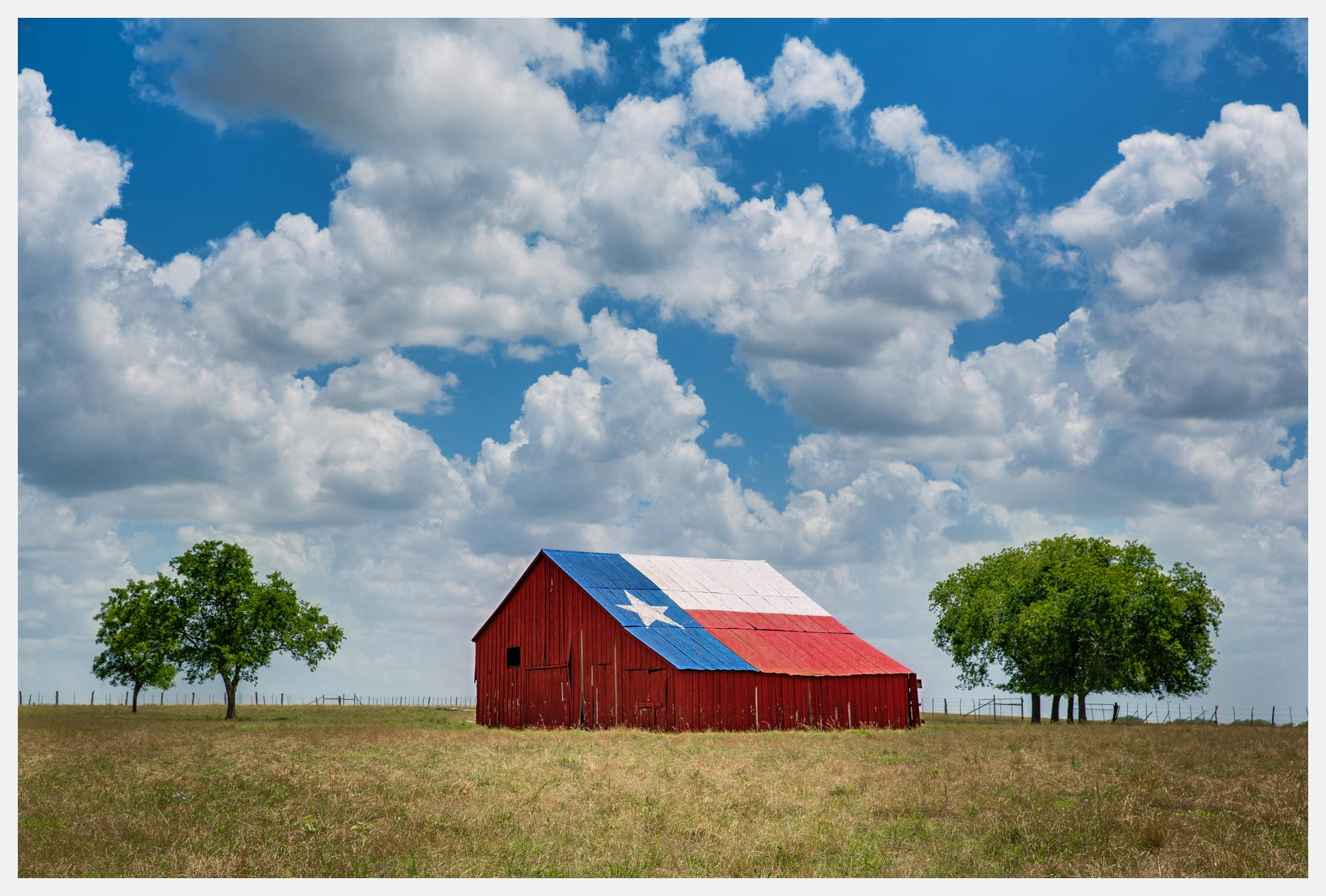 Texas Barn With Lone Star Flag and White Clouds