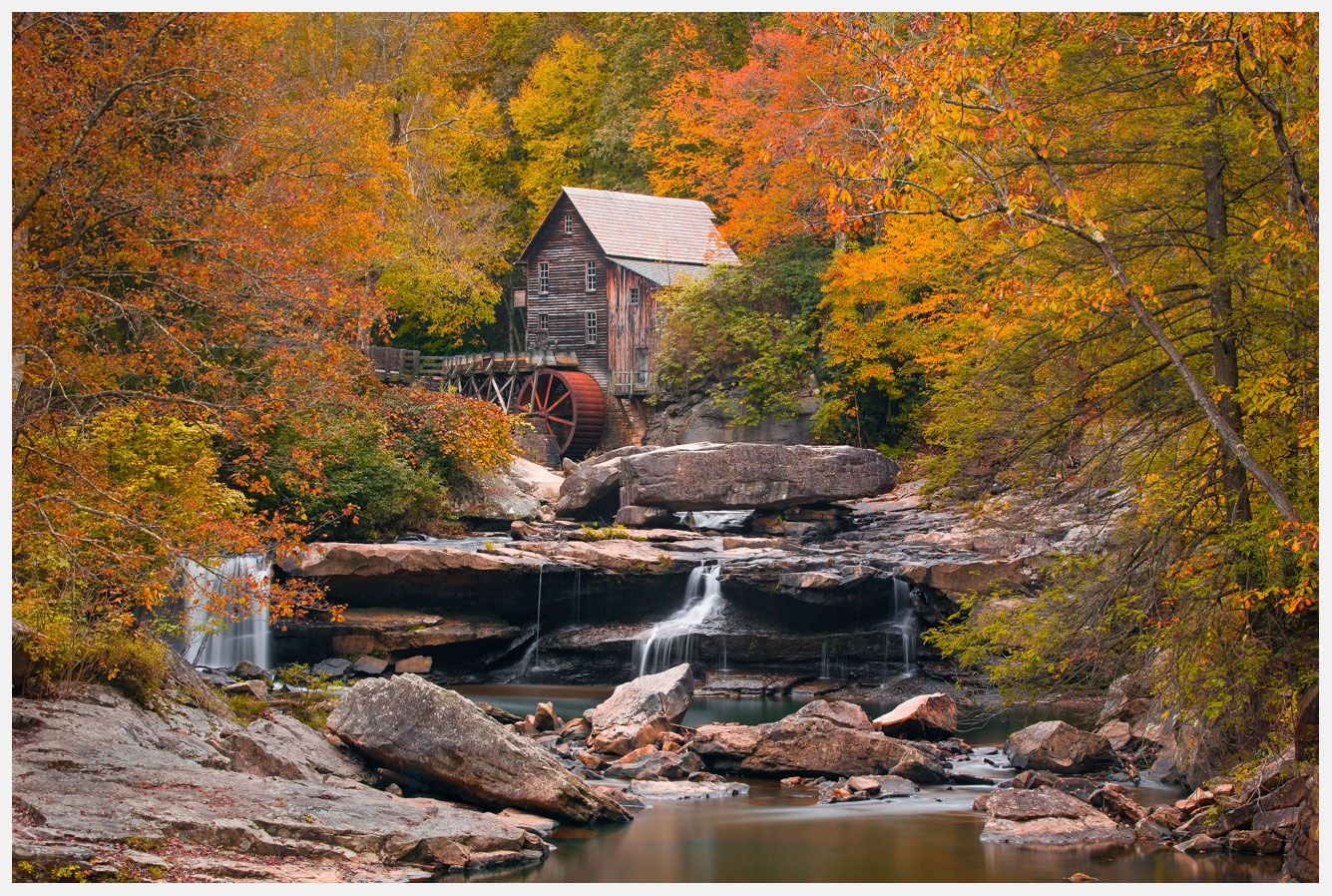 Autumn Leaves Next To A Stream With Water Flowing Over Rocks And A Mill In The Background,